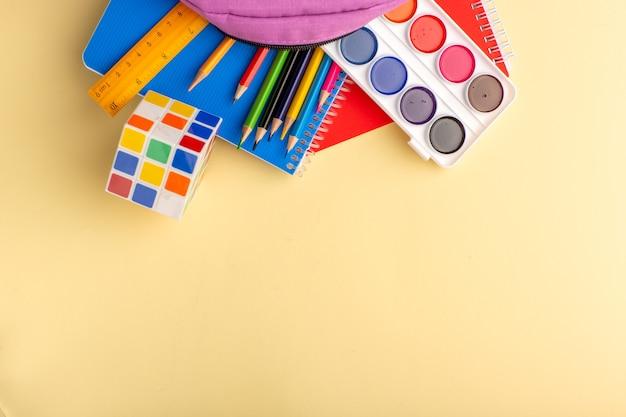 Vista de cima lápis coloridos com tintas para cadernos e bolsa roxa em um bloco de notas de caneta escolar amarelo claro.
