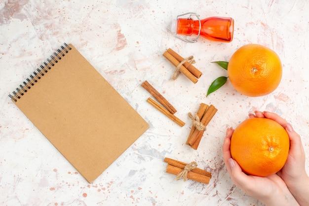 Vista de cima, laranjas frescas, paus de canela, laranja em mão feminina, garrafa de caderno na superfície brilhante