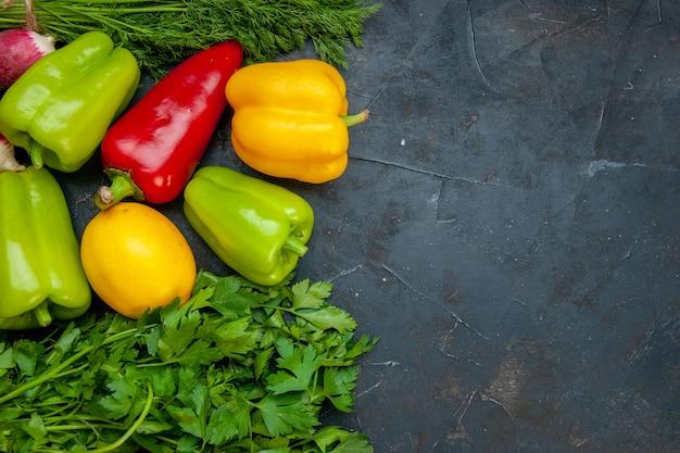 Vista de cima legumes cores diferentes, pimentão, limão, salsa, endro na mesa escura com espaço de cópia