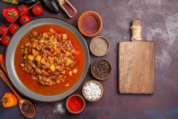 Vista de cima legumes cozidos fatiados com molho e temperos no fundo escuro refeição comida jantar sopa molho vegetal