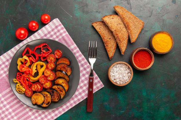 Vista de cima legumes fatiados cozidos, pimentões e berinjelas com temperos e pão na superfície verde