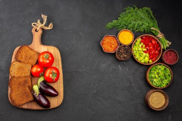 Vista de cima legumes frescos com pães escuros e temperos na superfície escura, salada, pão, comida