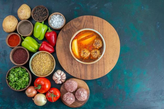 Vista de cima legumes frescos com temperos, sopa de carne e verduras na superfície azul escura