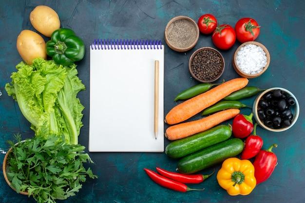 Vista de cima legumes frescos com verduras e bloco de notas na mesa azul-escura, almoço, salada, lanche, comida vegetal