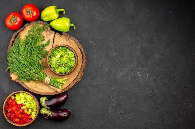 Vista de cima legumes frescos com verduras na superfície escura refeição madura salada vegetal saudável