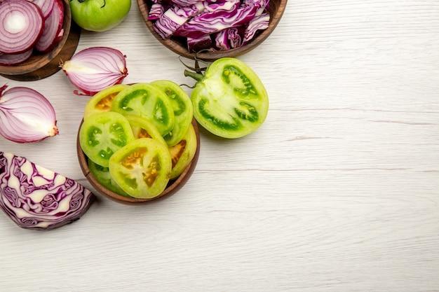 Vista de cima legumes frescos cortados tomates verdes cortados repolho roxo cebola cortada em tigelas na superfície de madeira branca com espaço livre