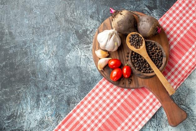 Vista de cima legumes frescos tomates cereja alho beterraba pimenta preta em uma tigela na placa de madeira no espaço livre da mesa cinza