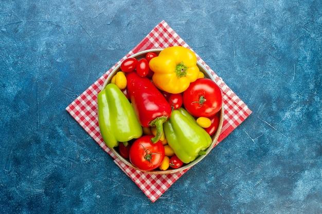 Vista de cima legumes frescos tomates cereja cores diferentes pimentões tomates cumcuat na bandeja na toalha de cozinha quadriculada branca vermelha na mesa azul com espaço de cópia