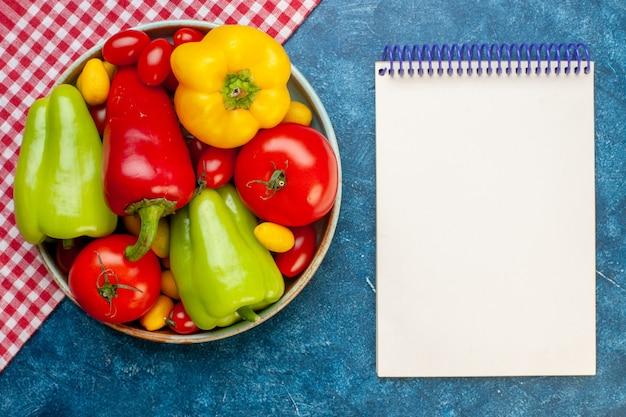 Vista de cima legumes frescos, tomates cereja, cores diferentes, pimentões, tomates, cumcuat, prato, vermelho e branco, toalha de mesa quadriculada, bloco de notas, sobre, azul, superfície