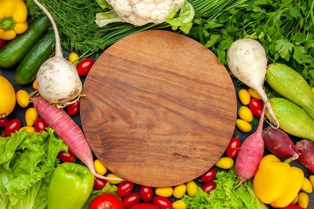 Vista de cima legumes frescos, tomates cereja, cumcuat, alface, endro, pimentão amarelo, pepino, abobrinha, tábua redonda de madeira no centro