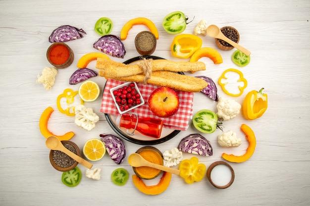 Vista de cima, legumes picados, pão de maçã, garrafa vermelha, guardanapo, prato branco, várias especiarias em pequenas tigelas na mesa