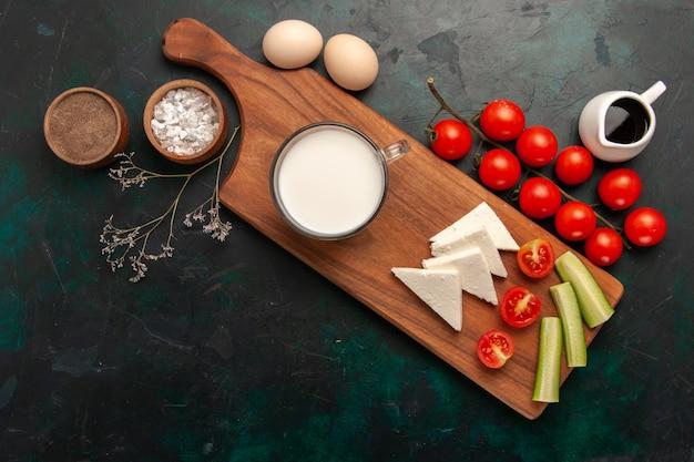 Vista de cima leite fresco com ovos crus e tomates frescos na superfície escura comida vegetal refeição café da manhã