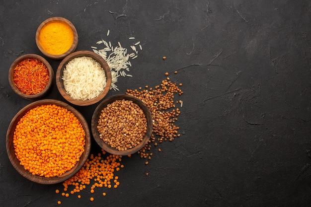 Vista de cima lentilha crua com trigo sarraceno na mesa escura