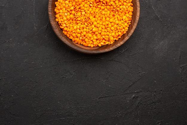 Vista de cima lentilha crua dentro do prato no espaço escuro
