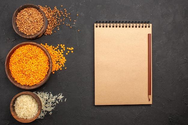 Vista de cima lentilha fresca crua com trigo sarraceno no espaço escuro