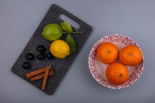 Vista de cima limão com limão e ameixa cereja e canela em uma tábua com laranjas em um prato sobre fundo cinza