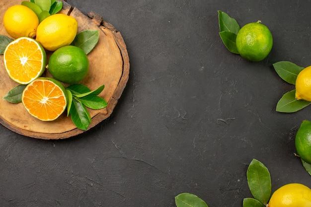 Vista de cima limões azedos frescos na mesa cinza-escuro com frutas cítricas e lima