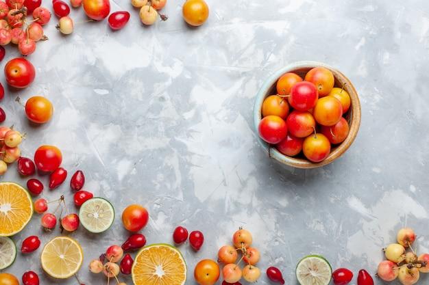 Vista de cima, limões e cerejas, frutas frescas com pote de ameixas cereja na mesa de luz frutas frescas maduras