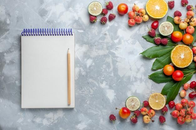 Vista de cima, limões e cerejas, frutas frescas, juntamente com o bloco de notas na mesa de luz, frutas frescas maduras