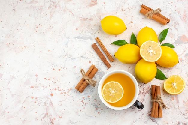 Vista de cima limões frescos cortados em palitos de canela com limão, uma xícara de chá de limão em uma superfície brilhante e isolada.
