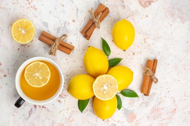 Vista de cima limões frescos cortados em palitos de canela e limão uma xícara de chá de limão na superfície brilhante e isolada