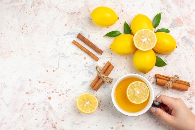 Vista de cima limões frescos cortados em paus de canela e limão uma xícara de chá de limão na mão de uma mulher em uma superfície isolada brilhante. Foto gratuita