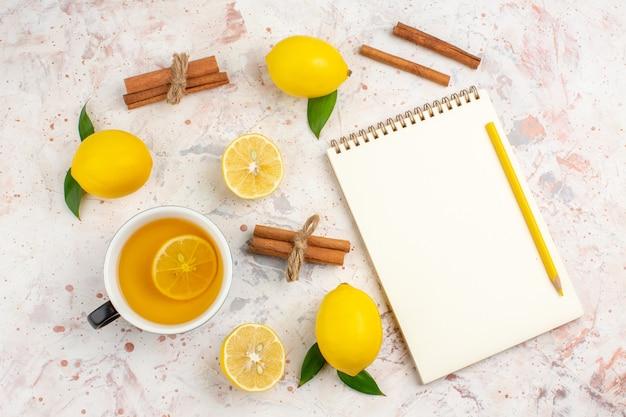 Vista de cima limões frescos cortados em paus de canela e limão uma xícara de chá de limão no bloco de notas em uma superfície isolada brilhante