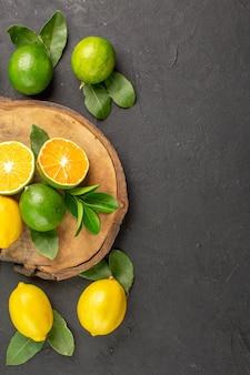 Vista de cima limões frescos em mesa escura limas frutas cítricas