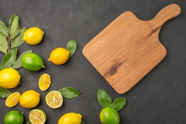 Vista de cima, limões frescos, frutas ácidas em frutas cítricas e lima, de mesa escura