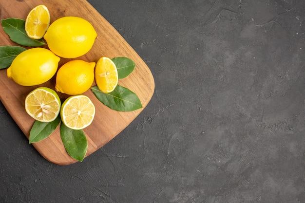 Vista de cima, limões frescos, frutas ácidas em uma mesa cinza-escuro com lima cítrica
