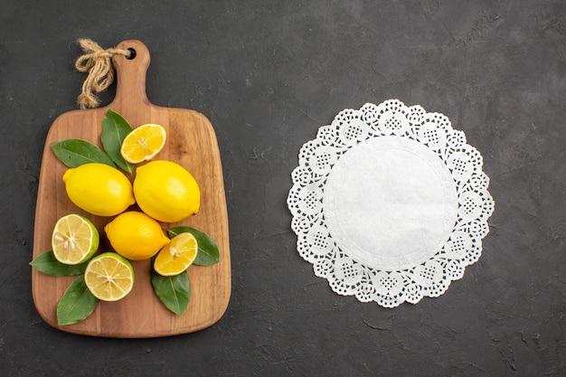 Vista de cima limões frescos frutas ácidas na mesa cinza-escuro frutas cítricas lima