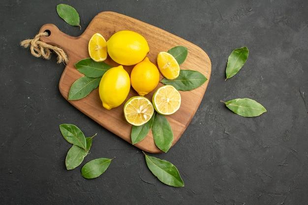 Vista de cima, limões frescos, frutas ácidas na mesa escura de lima
