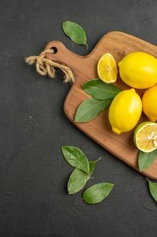 Vista de cima limões frescos frutas ácidas na mesa escura lima cítrica madura