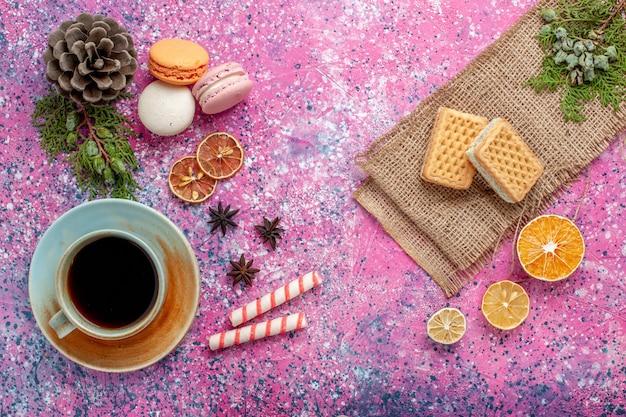 Vista de cima macarons franceses deliciosos bolinhos com waffles e chá na superfície rosa