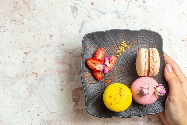 Vista de cima macarons franceses dentro do prato no bolo doce de biscoito de mesa branca