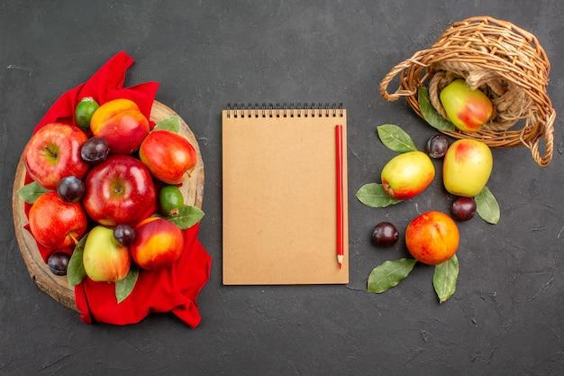Vista de cima maçãs frescas com pêssegos e ameixas na mesa escura.
