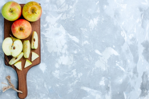 Vista de cima, maçãs frescas cortadas em fatias de frutas inteiras na superfície branca