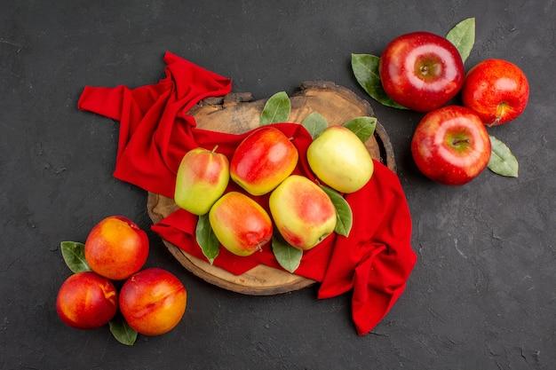 Vista de cima maçãs frescas frutas maduras em tecido vermelho e mesa cinza frutas maduras frescas