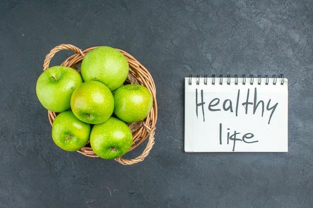 Vista de cima maçãs frescas na cesta de vime vida saudável escrita no bloco de notas na superfície escura