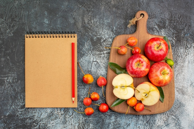 Vista de cima, maçãs, tábua de cortar, maçãs, cerejas, lápis, caderno