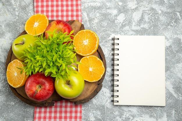 Vista de cima maçãs verdes frescas com laranjas fatiadas na superfície branca frutas maduras frescas de maçã