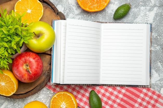 Vista de cima maçãs verdes frescas com laranjas fatiadas na superfície branca maçãs frutas maduras frescas