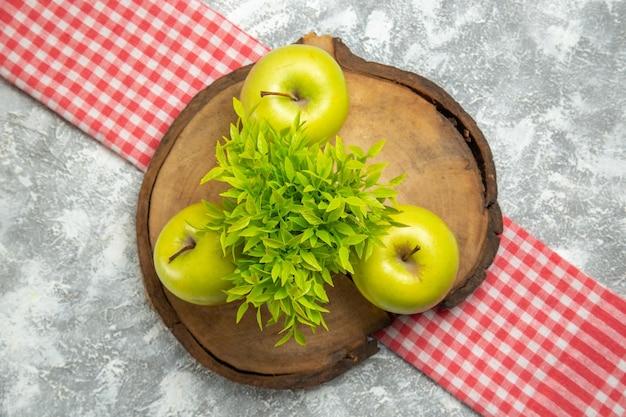 Vista de cima maçãs verdes frescas com planta verde na superfície branca maçãs maduras maduras frescas