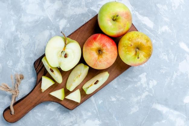 Vista de cima maçãs verdes frescas cortadas e frutas inteiras em superfície branca