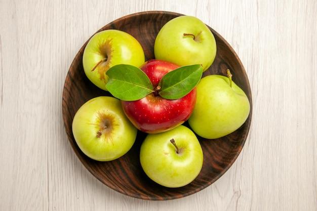 Vista de cima maçãs verdes frescas frutas maduras e maduras na mesa branca cor de frutas planta fresca árvore vermelha