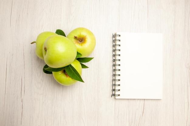 Vista de cima maçãs verdes frescas frutas maduras e maduras na mesa branca planta cor da fruta árvore verde fresca
