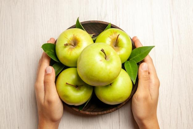 Vista de cima maçãs verdes frescas frutas maduras e maduras na mesa branca planta frutas coloridas árvore verde fresca