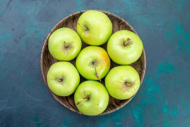 Vista de cima, maçãs verdes, frutas frescas e suaves na mesa azul escura
