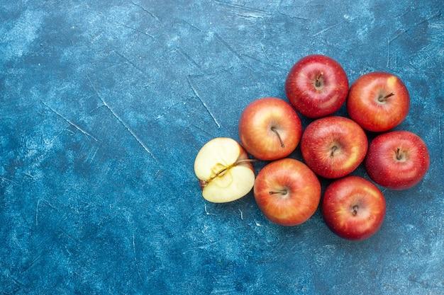 Vista de cima maçãs vermelhas frescas alinhadas com frutas maduras de mesa azul