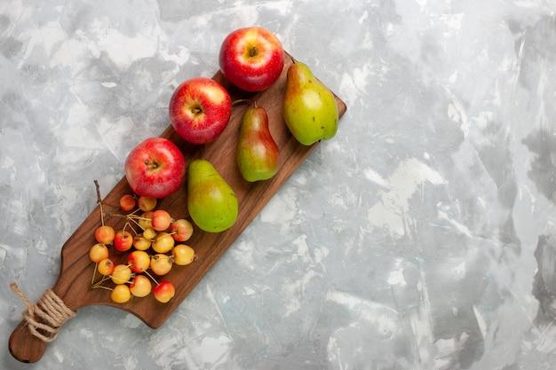 Vista de cima maçãs vermelhas frescas com cerejas e peras na mesa branca.